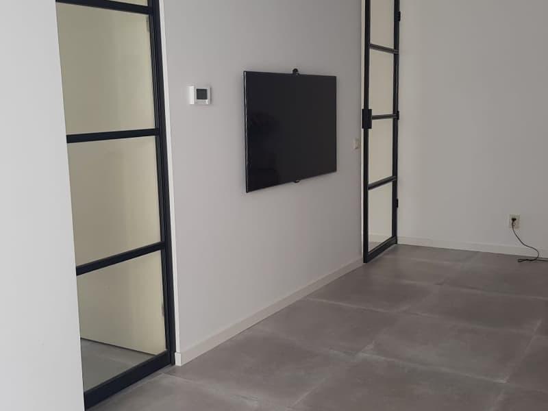 Zwarte Stalen Deuren met Lichte Betonlook Tegels in de Woonkamer - T&L