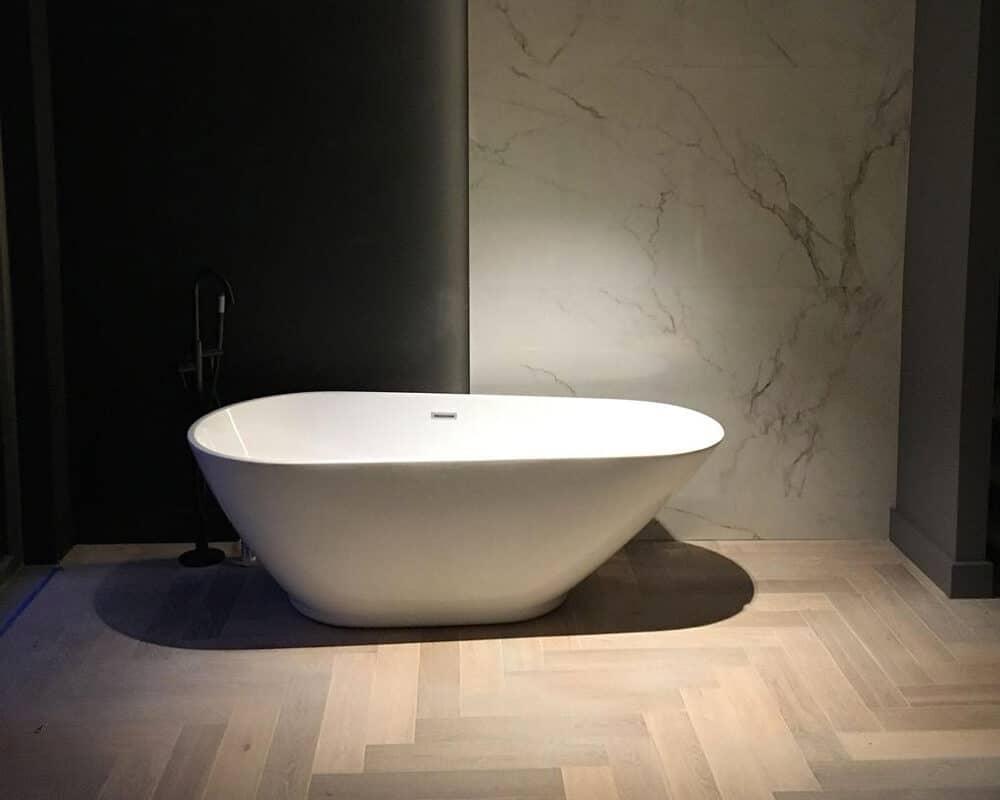 Visgraat houtlook tegels met grote marmerlook tegels in de badkamer